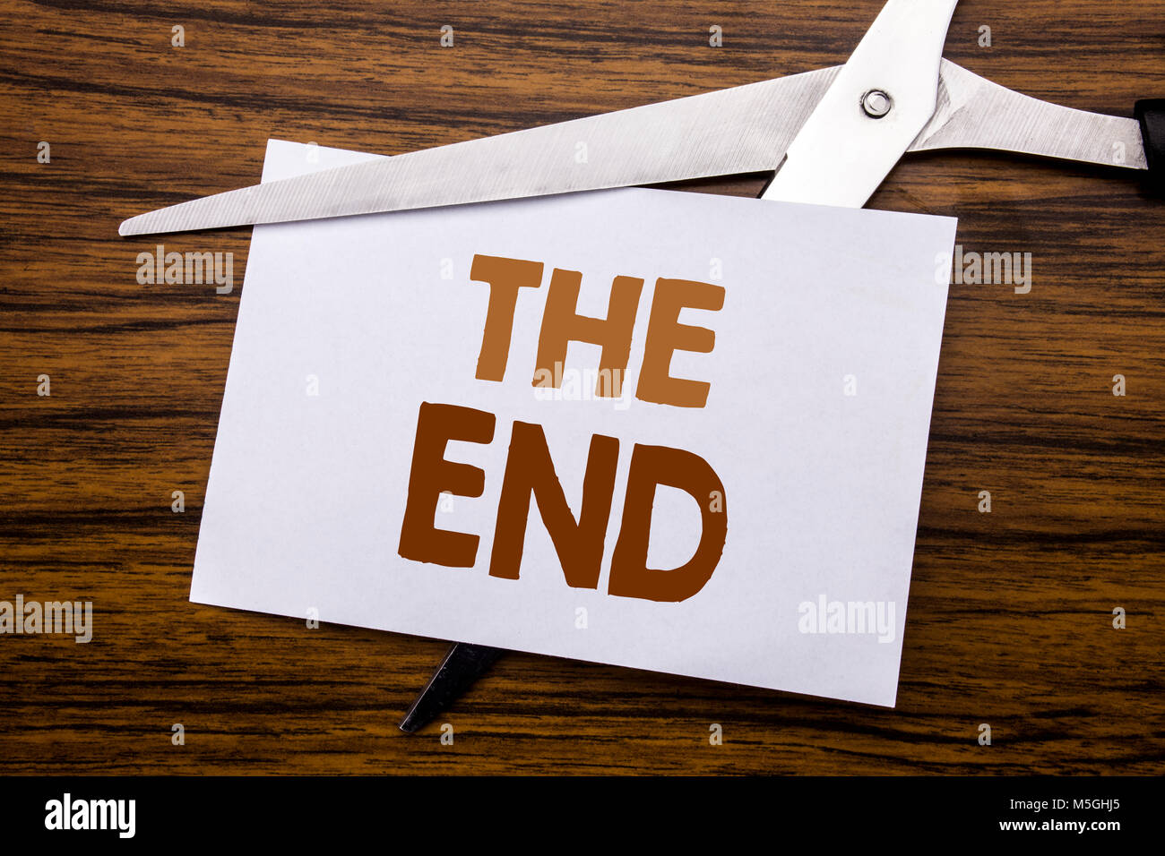 Hand writing text caption inspiration showing The End. Business concept for End Finish Close Written on note, wooden - Stock Image