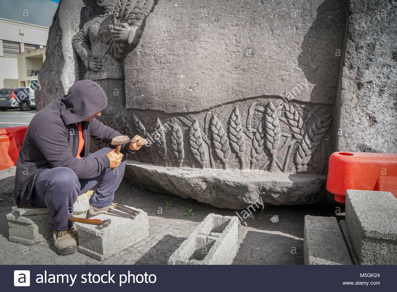 a large stone is being worked by a sculptor in Povoação, Sao Miguel, Azores - Stock Image