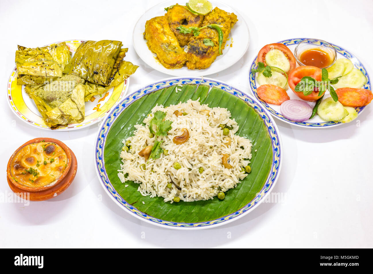 Popular delicious Bengali Indian cuisine meal with vegetable fried rice , spicy fish curry, salads and sweet dish. - Stock Image