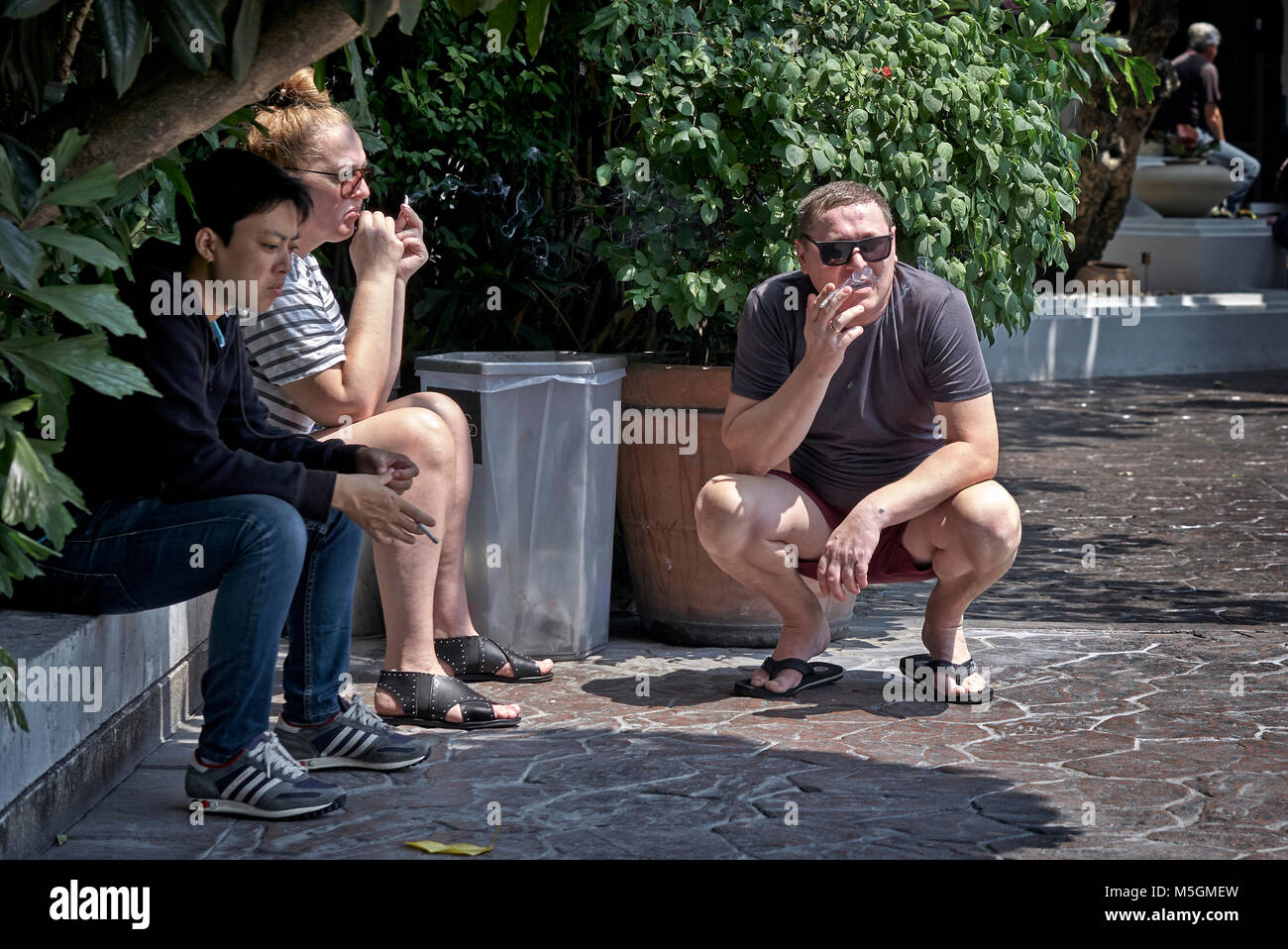 Smokers. People smoking cigarettes in the outdoor smoking area Stock Photo