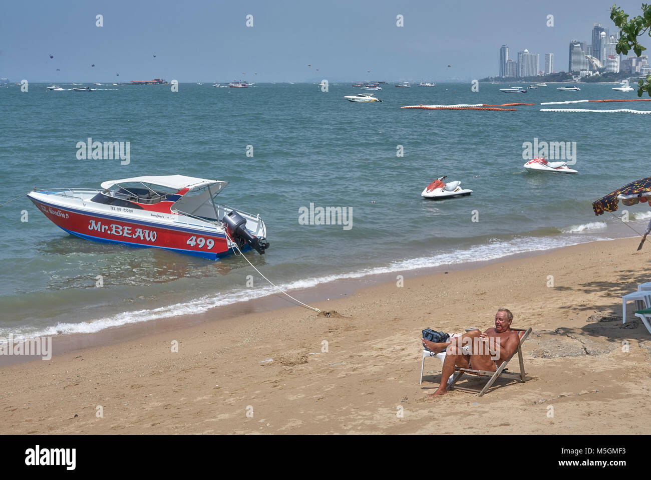 Man relaxing alone on the beach. Pattaya beach, Thailand, Southeast Asia. - Stock Image