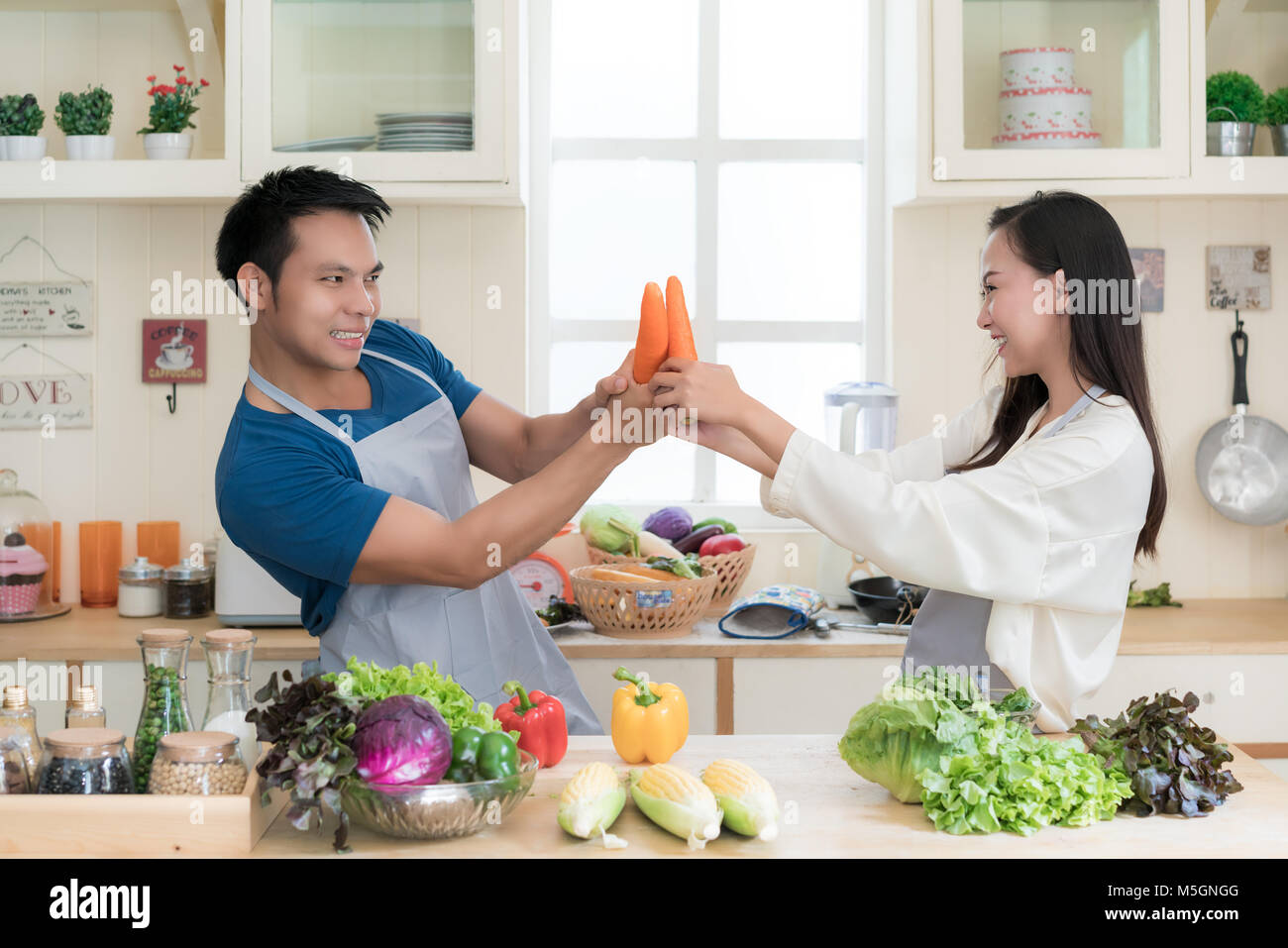Fun Asian couple mock fighting with carrots as Asian couple cook healthy meal together using fresh vegetables and - Stock Image