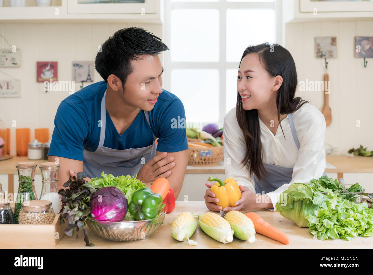 Young Asian couple preparing food together at counter in kitchen. Happy love couple concept. - Stock Image