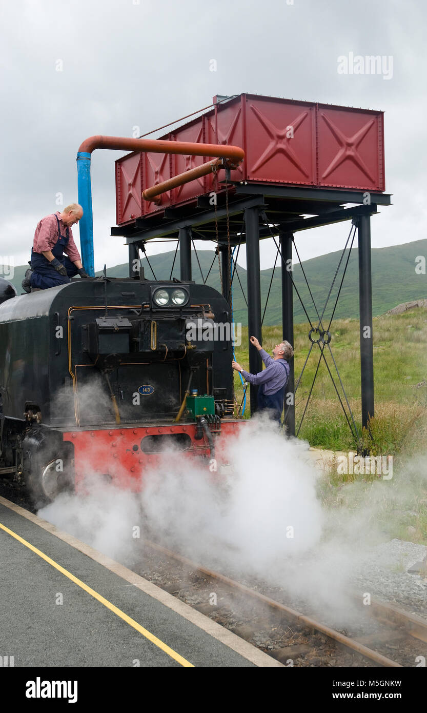 Refilling the water tank on the Welsh Highland Railway line between Caernarfon and Porthmadog - Stock Image