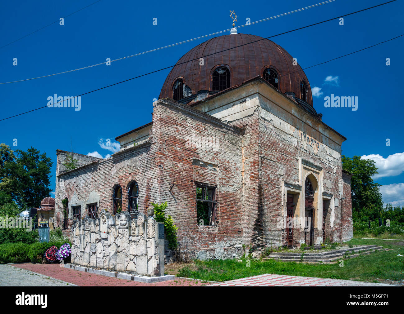 Ruined synagogue, memorial wall constructed of fragments of headstones, Jewish Cemetery in Chernivtsi, Bukovina - Stock Image