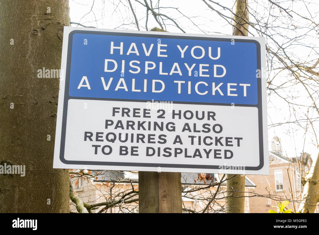 Sign warning that a ticket is required for free parking - Bearsden, Glasgow, Scotland, UK - Stock Image