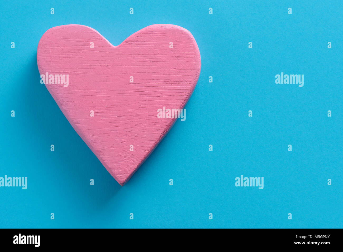closeup of a pink three-dimensional heart on a blue background, with a blank space on the right - Stock Image