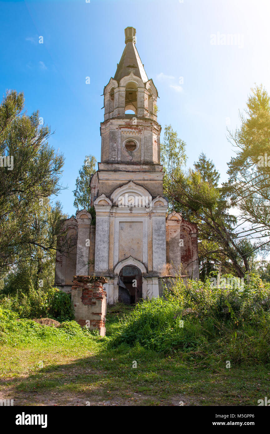 The ruins of old Christian Church on a background of bright trees and a blue sky. - Stock Image