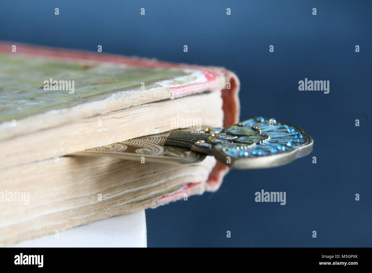 Close up fine art photo of an art deco bookmark in pages of an old book Stock Photo