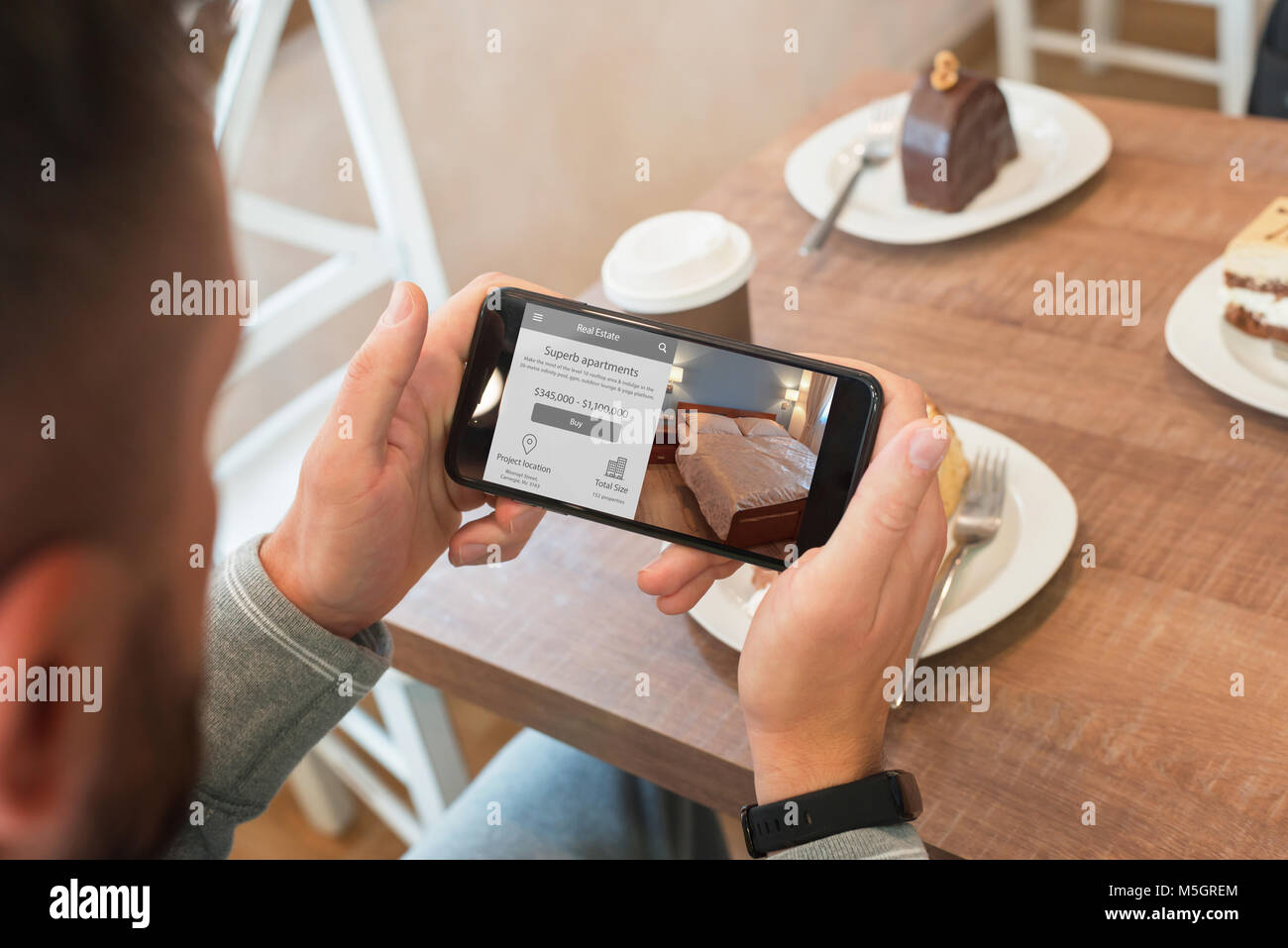 Property Agent Use Agency Web Site With Mobile Phone To Find Apartment.  Coffee Shop In Background.