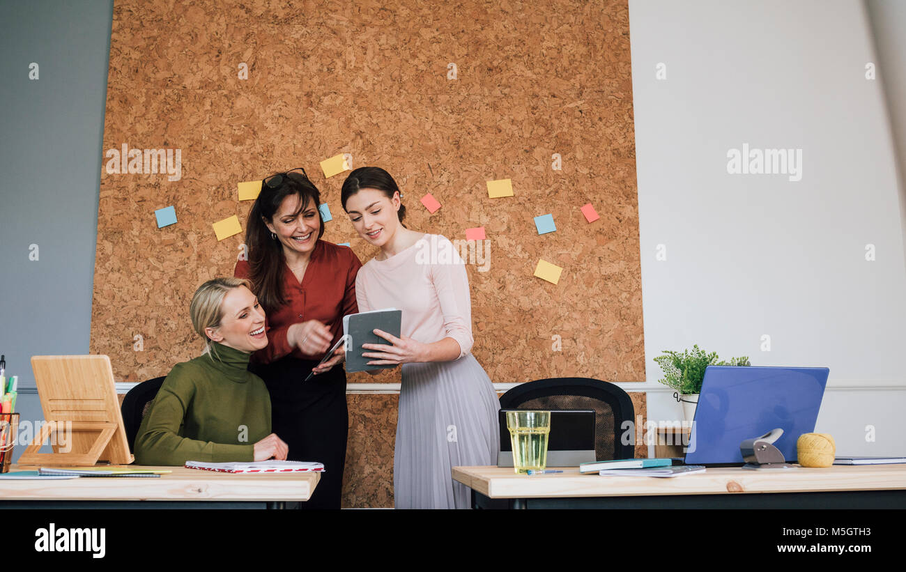 Women are working together in an office. One of the women is holding a digital tablet which they are all looking - Stock Image