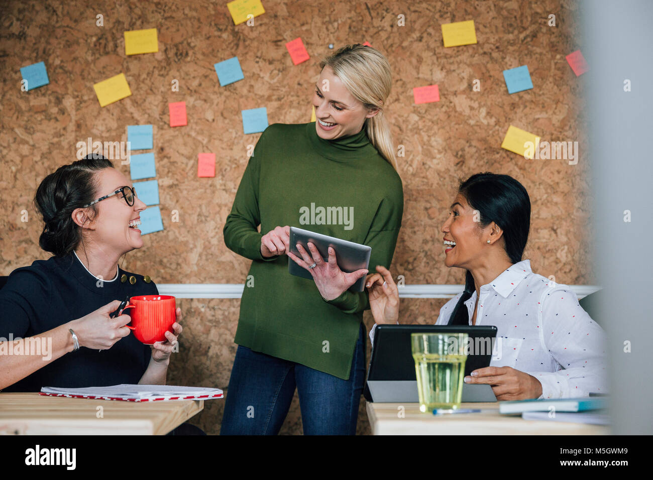 Women are working together in an office. They are talking and laughing as they use digital tablets. - Stock Image