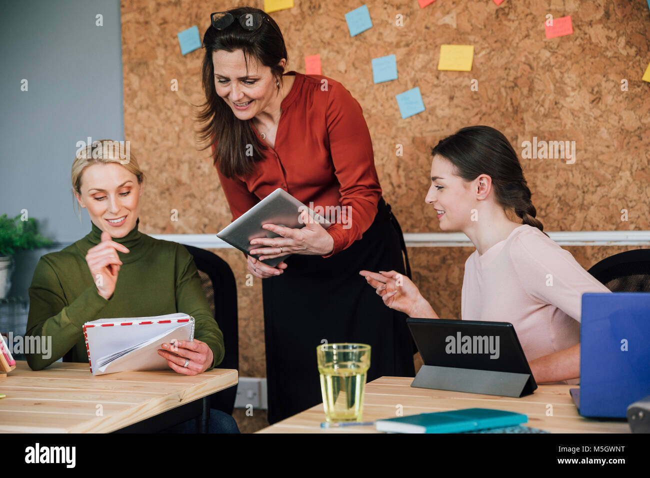 Women are working together in an office. They are talking as they use digital tablets. - Stock Image