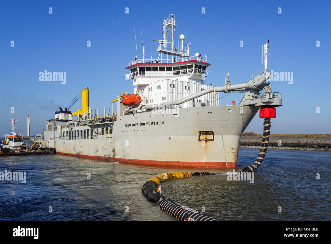 Trailing suction hopper dredger Alexander von Humboldt in port of Ostend discharging sand via long hoses / floating - Stock Image