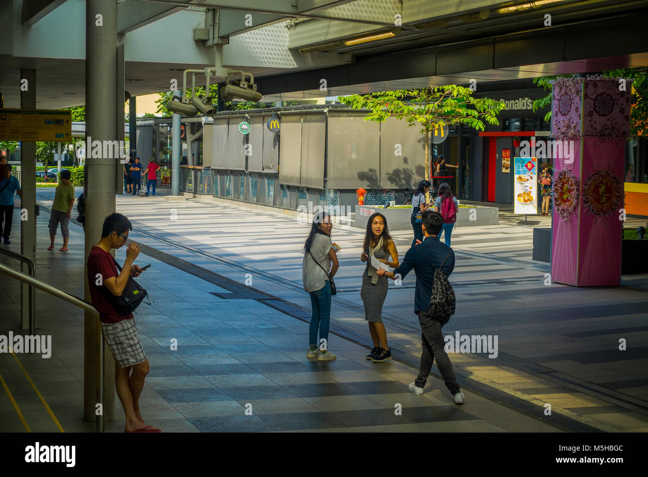 SINGAPORE, SINGAPORE - JANUARY 30, 2018: Outdoor view of unidentified people walking in the sidewalks close to at Stock Photo