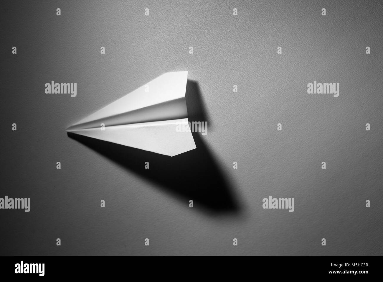 The paper plane with a dramatic light - Stock Image