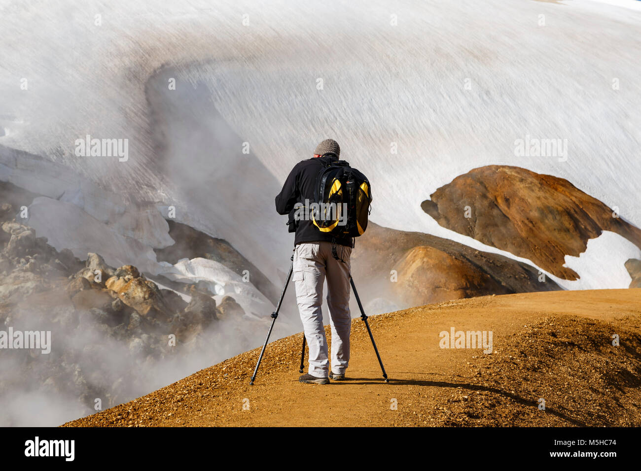 Photographer with tripod photographing rhyolite mountains partially covered in snow and fumaroles, Kerlingarfjoll, - Stock Image