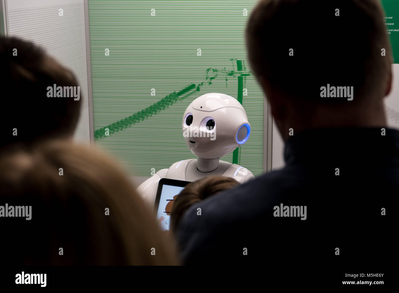 People looking at a robot looking at people - Stock Image