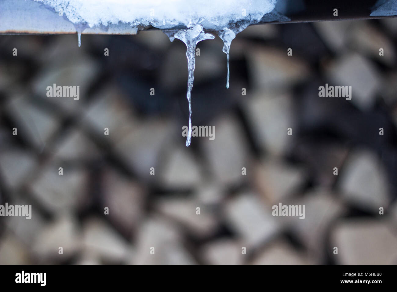 icicles and firewood in the background - Stock Image