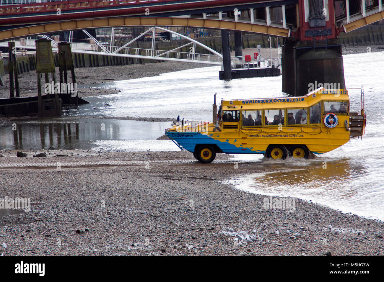A yellow amphibian tour vehicle called a Duck, leaving the River Thames, London, England, UK. Credit: London Snapper - Stock Image