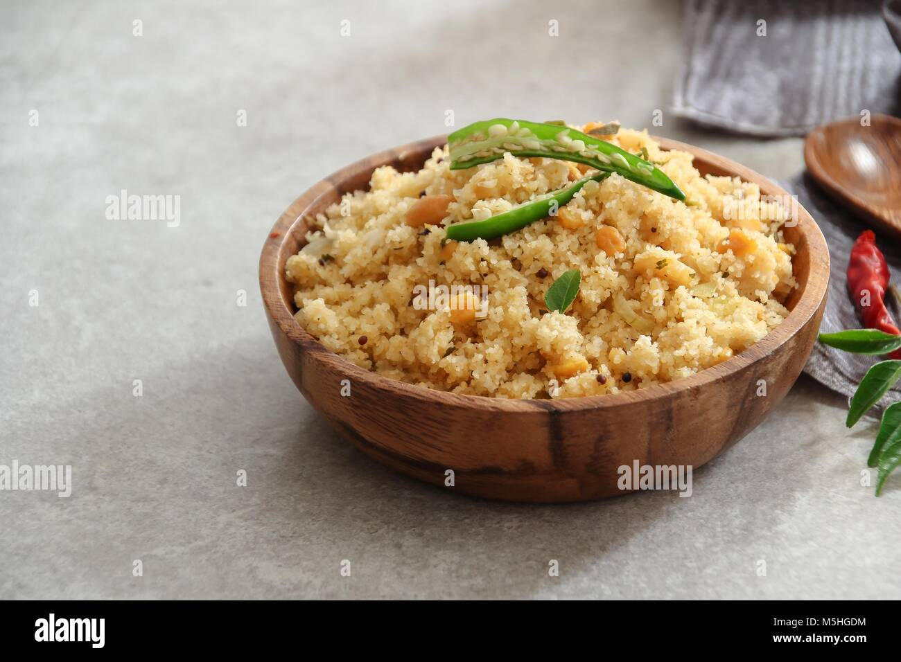 Rava Upma - south indian breakfast with semolina served in a wooden bowl - Stock Image