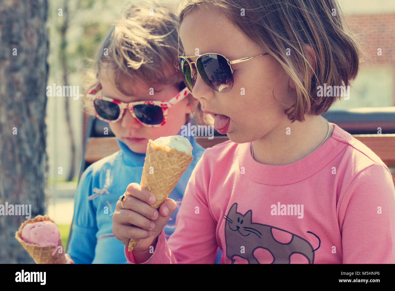 Two little girls (sisters) eating ice cream. - Stock Image