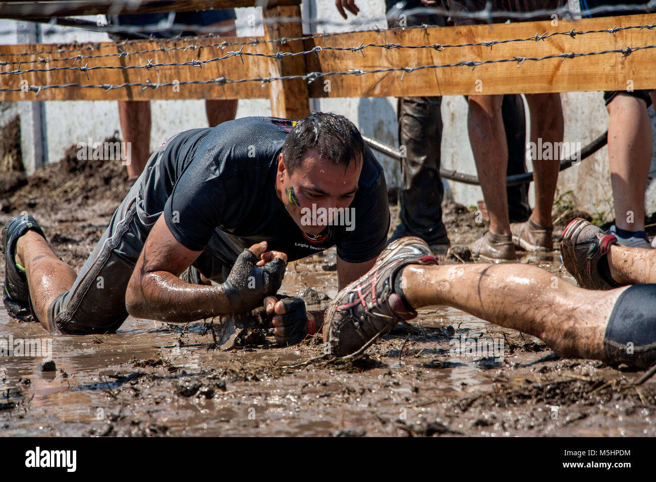 A man crawling under barbed wire during strength race Legion Run held  in Sofia, Bulgaria on 26 July 2014 - Stock Image