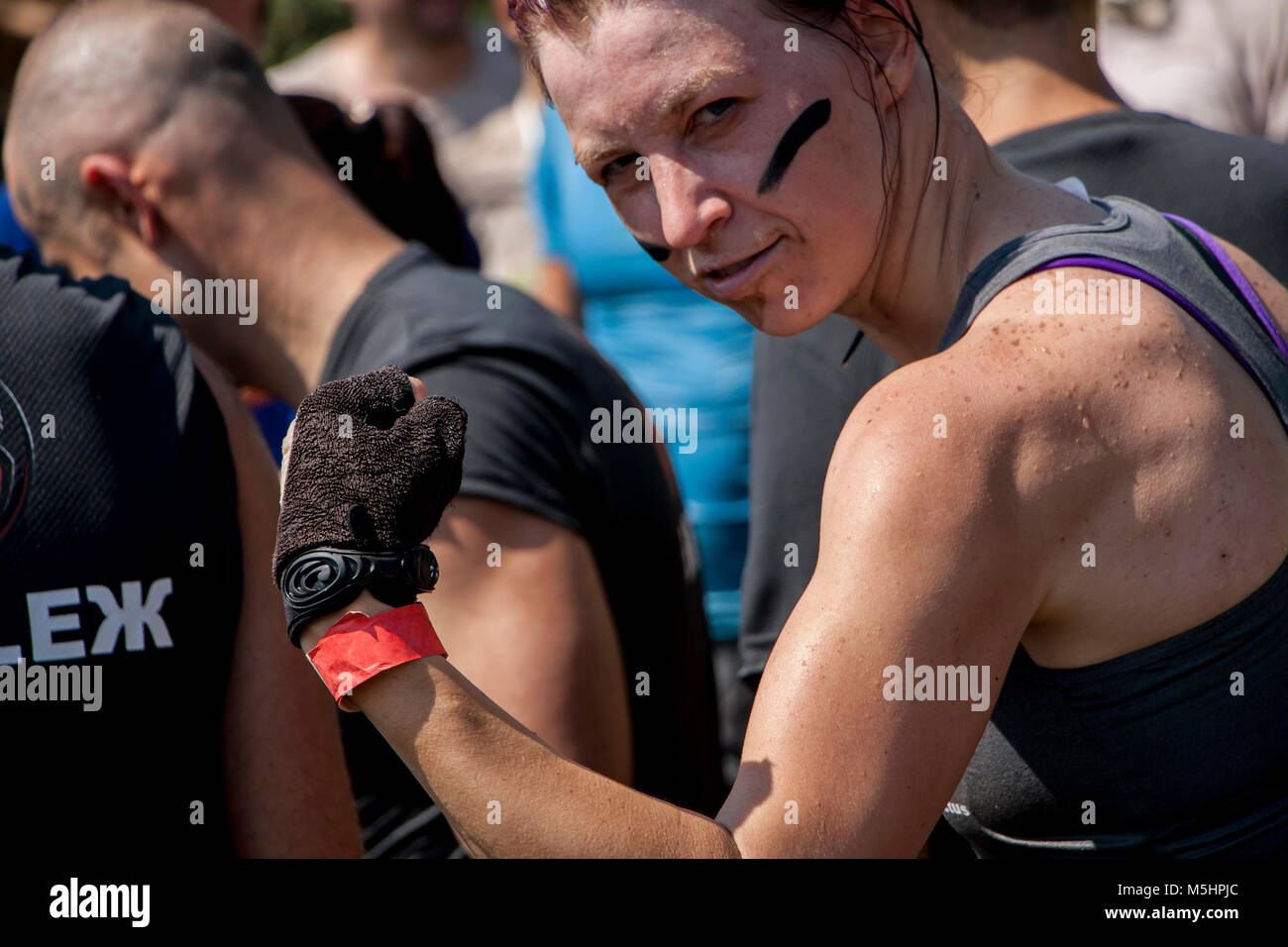 A woman is showing her muscles during physical competition Legion Run held in Sofia, Bulgaria on 26 July 2014 - Stock Image