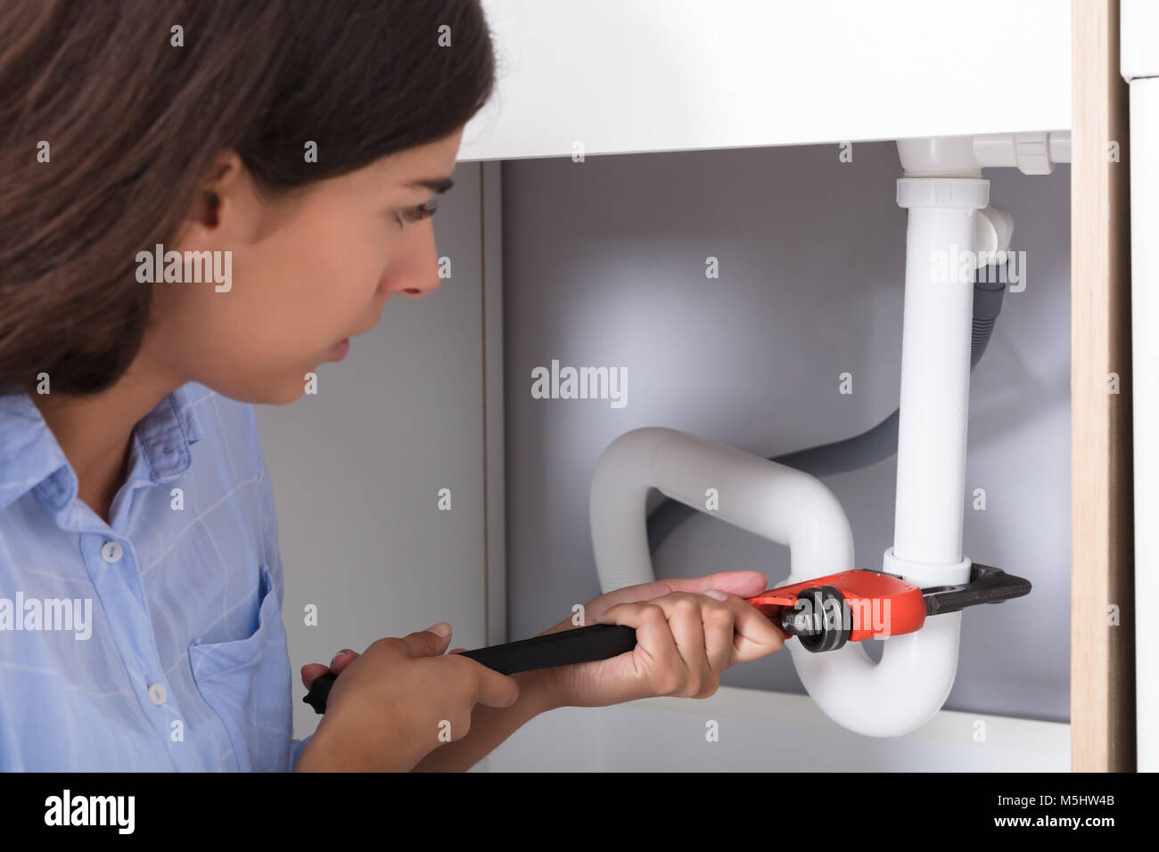 Close-up Of Young Woman Tightening Sink Pipe With Monkey Wrench In Kitchen - Stock Image