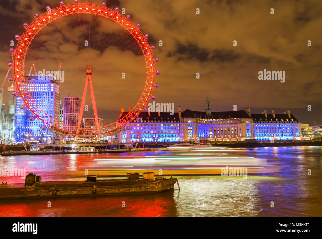 London, United Kingdom, February 17, 2018: UK skyline in the evening. Ilumination of the London Eye and the buildings - Stock Image