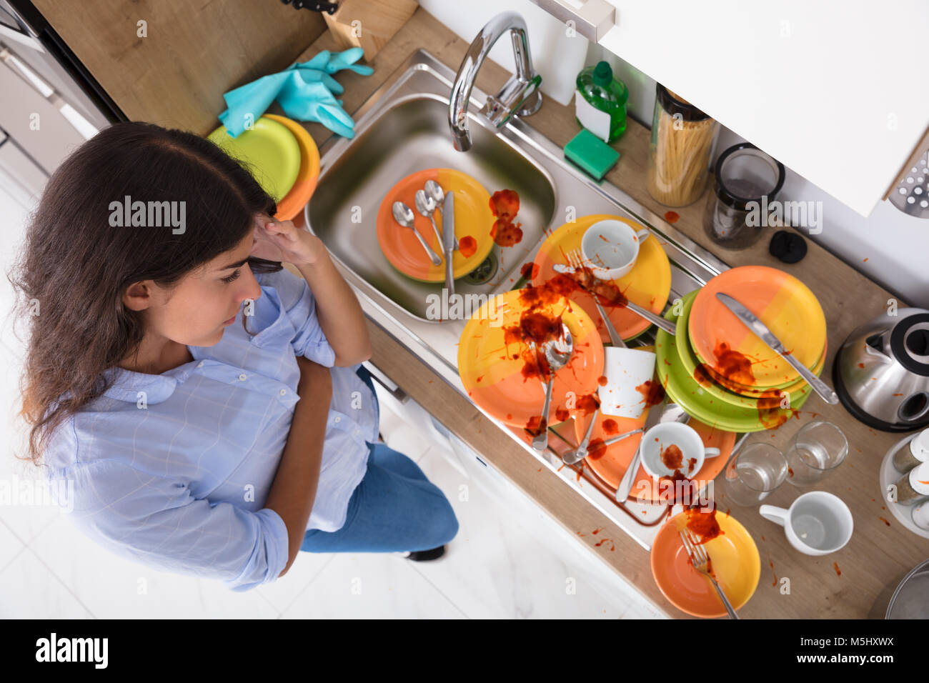 High Angle View Of Stressed Young Woman Looking At Unwashed Utensils In Kitchen - Stock Image