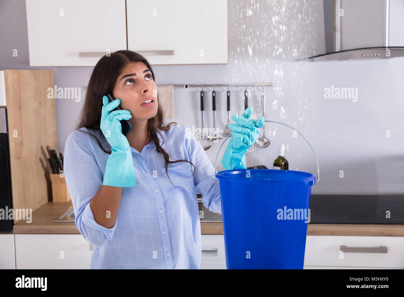 Woman Calling Plumber While Collecting Water Leaking From Ceiling Using Bucket Stock Photo