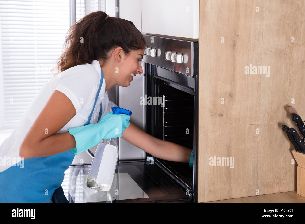 Beautiful Woman In Protective Gloves Cleaning Oven With Spray Bottle And Rag Stock Photo