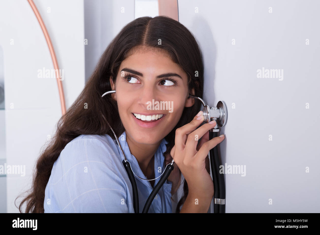 Young Curious Women Listening Through Wall Using Stethoscope - Stock Image