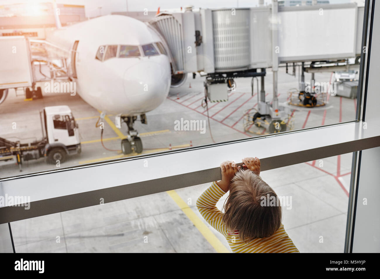 Little girl looking through window to airplane on the apron - Stock Image