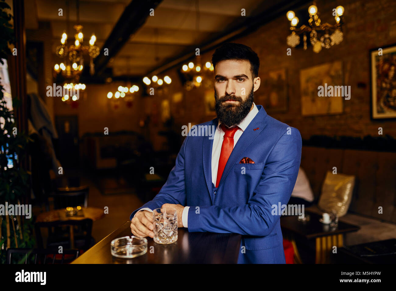 Portrait of elegant young man in a bar with tumbler - Stock Image