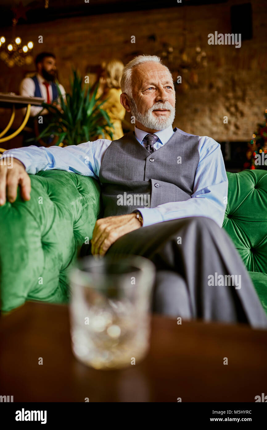 Portrait of elegant senior man sitting on couch in a bar - Stock Image