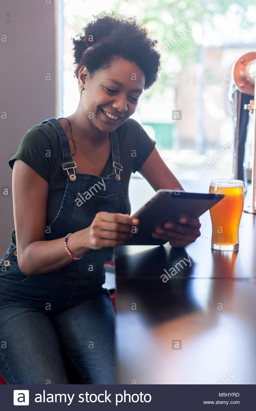 Black woman in a beer bar looking at tablet Stock Photo