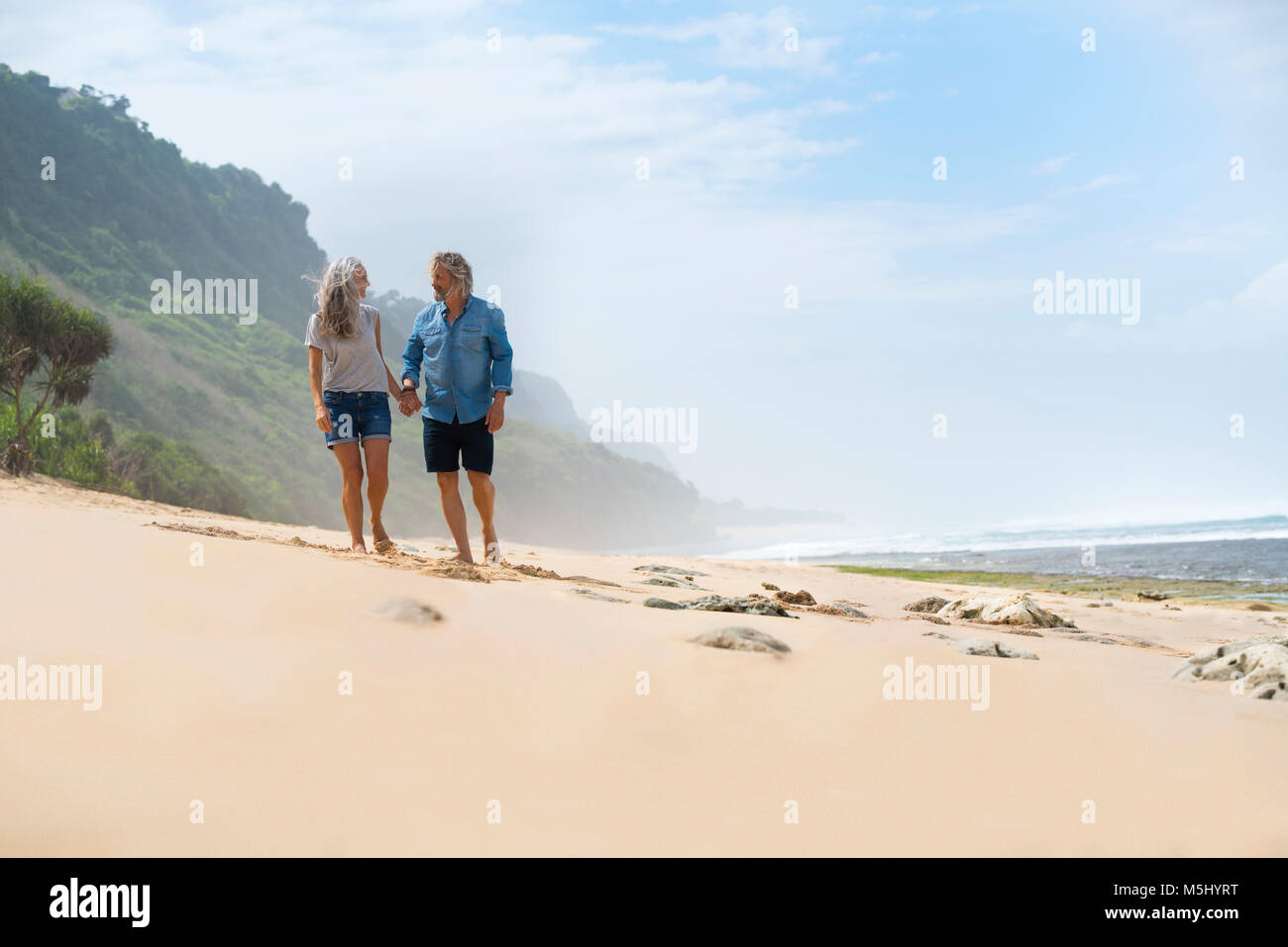Affectionate senior couple walking on the , holding hands - Stock Image