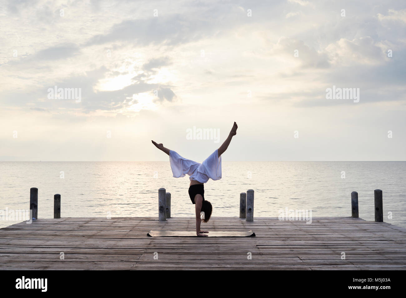 Yoga instructor standing upside down on hands while doing yoga against sunset and sea. Kep, Cambodia. - Stock Image