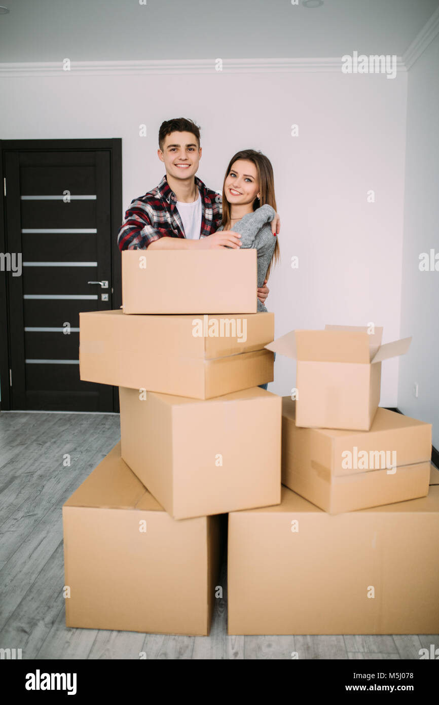 Happy young couple moved to new place to start live together, they are embracing, around many carton boxes with - Stock Image