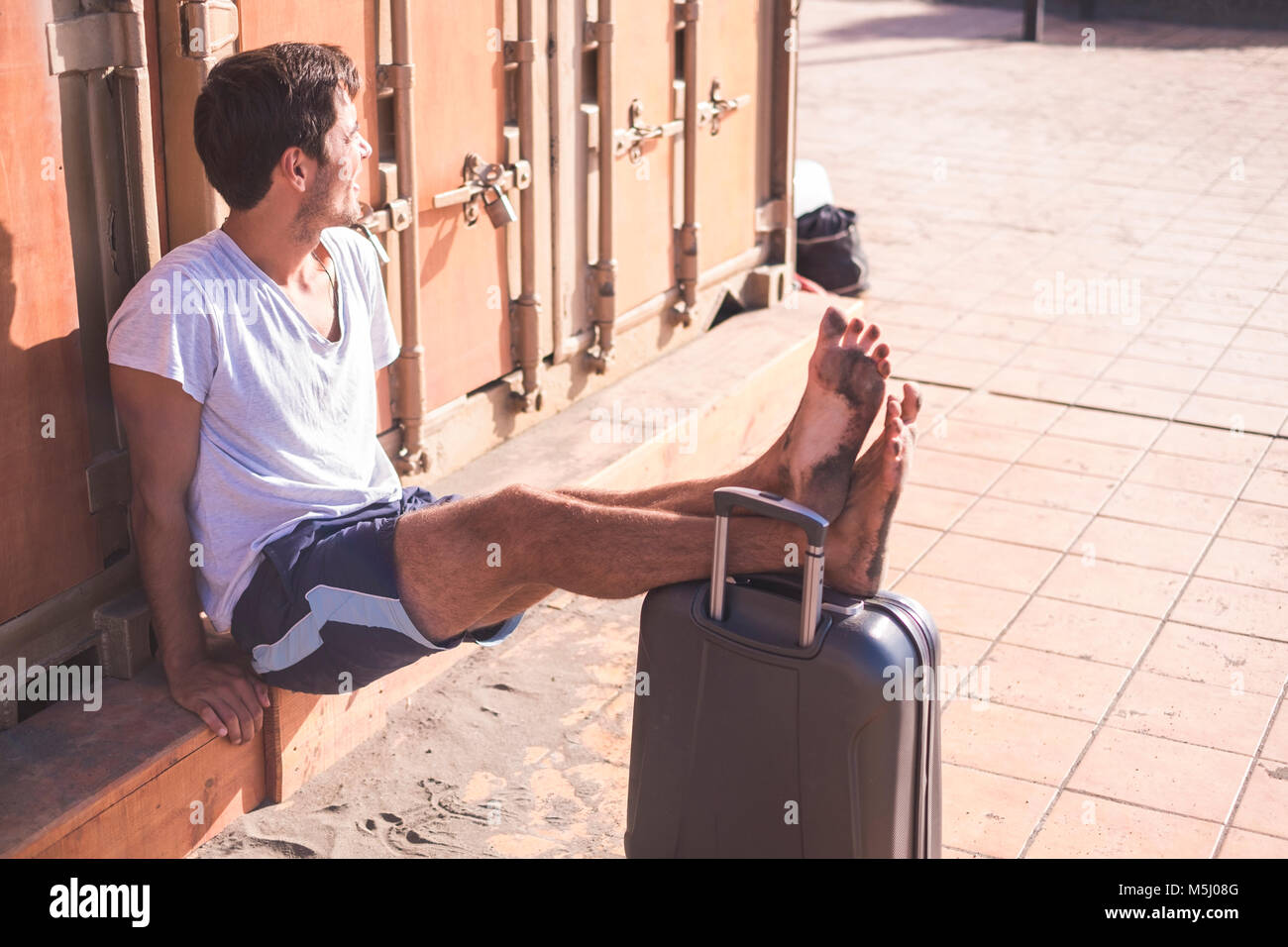 Barefeet man with rolling suitcase sitting in front of cubicle - Stock Image