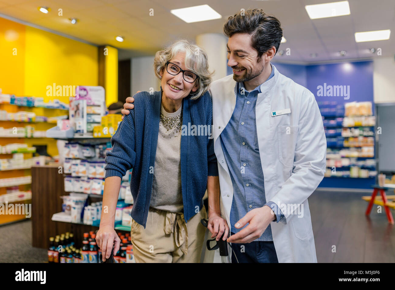 Portrait of smiling pharmacist and customer with wheeled walker in pharmacy - Stock Image