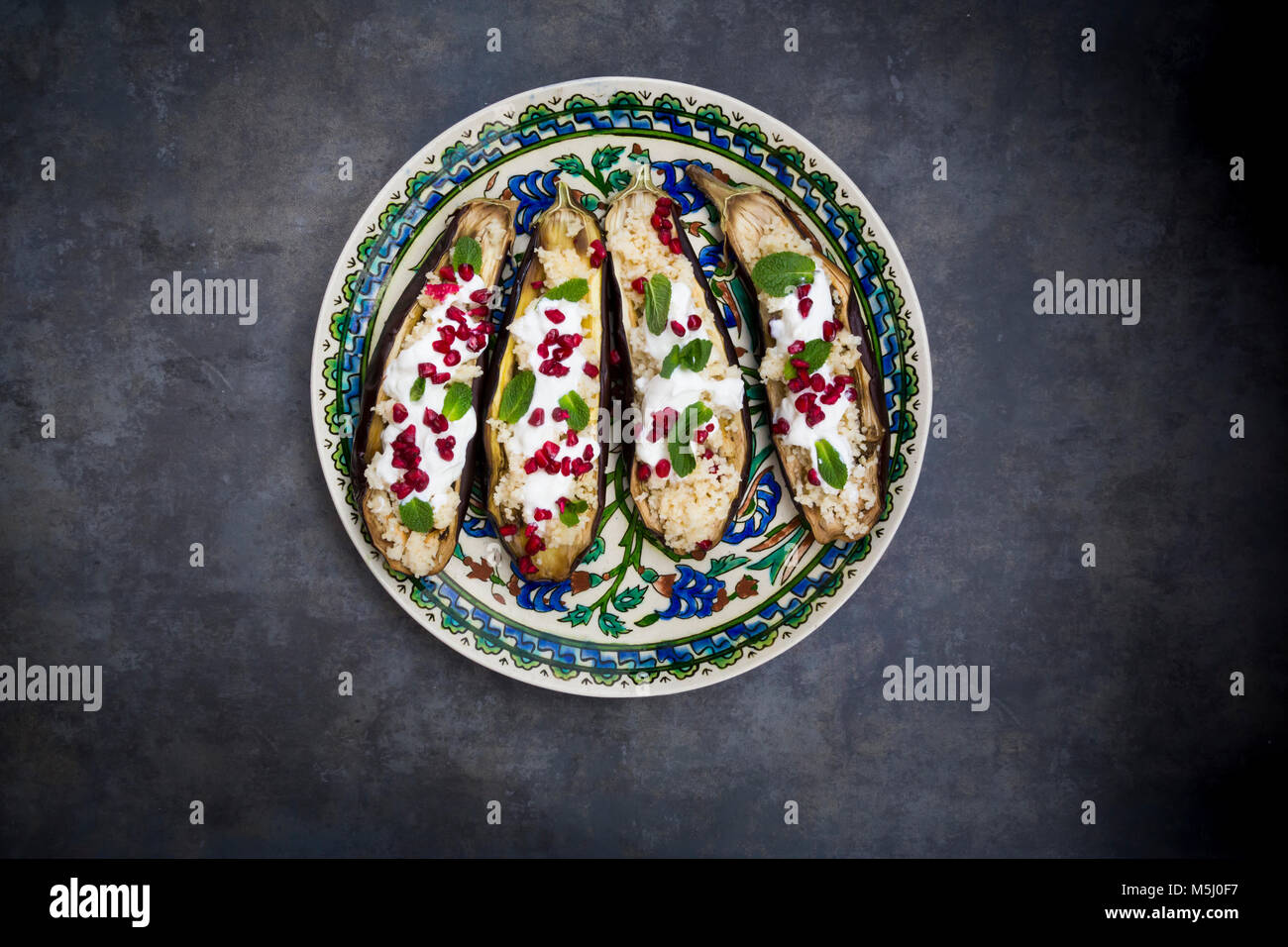 Filled aubergine, couscous, yogurt sauce, mint and pomegranate seeds - Stock Image