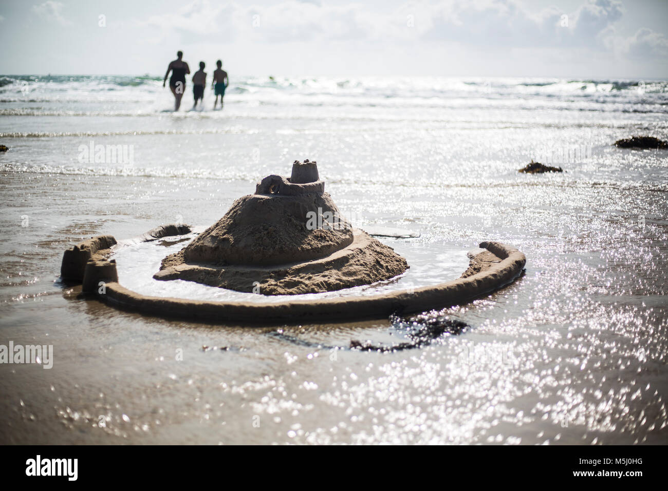 France, Normandy, Portbail, Contentin, sand castle on the beach and family in background - Stock Image