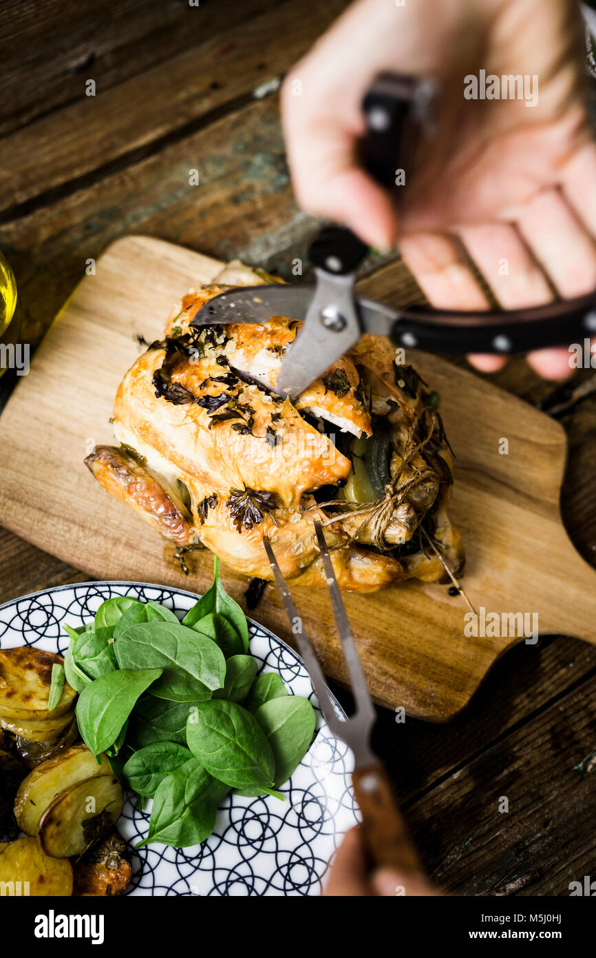 Woman jointing freshly cooked chicken - Stock Image