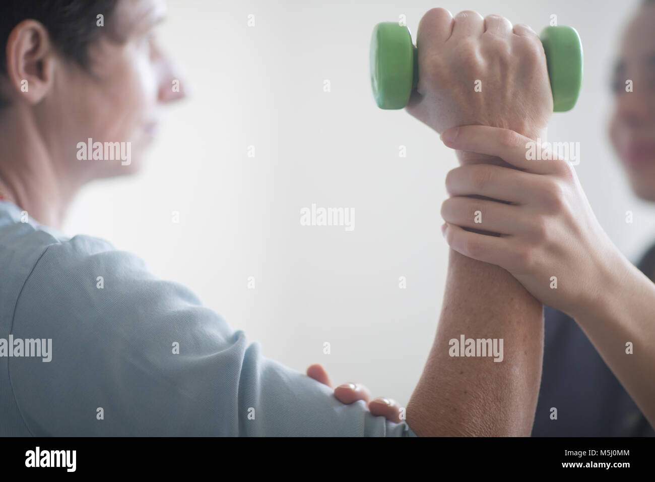 Physiotherapist and patient, training with dumbbell - Stock Image