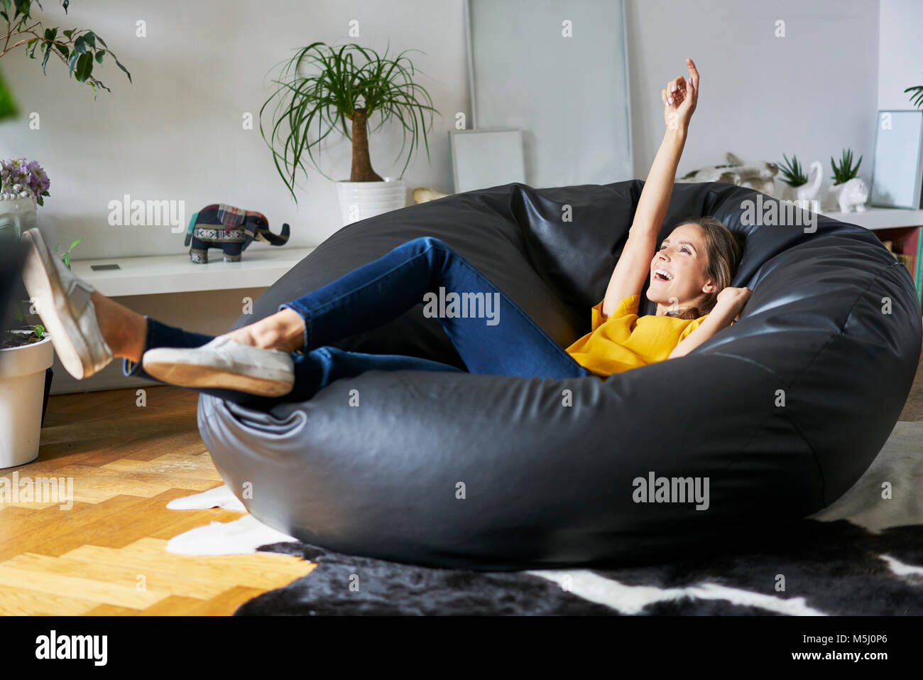 Happy young woman relaxing at home in beanbag - Stock Image