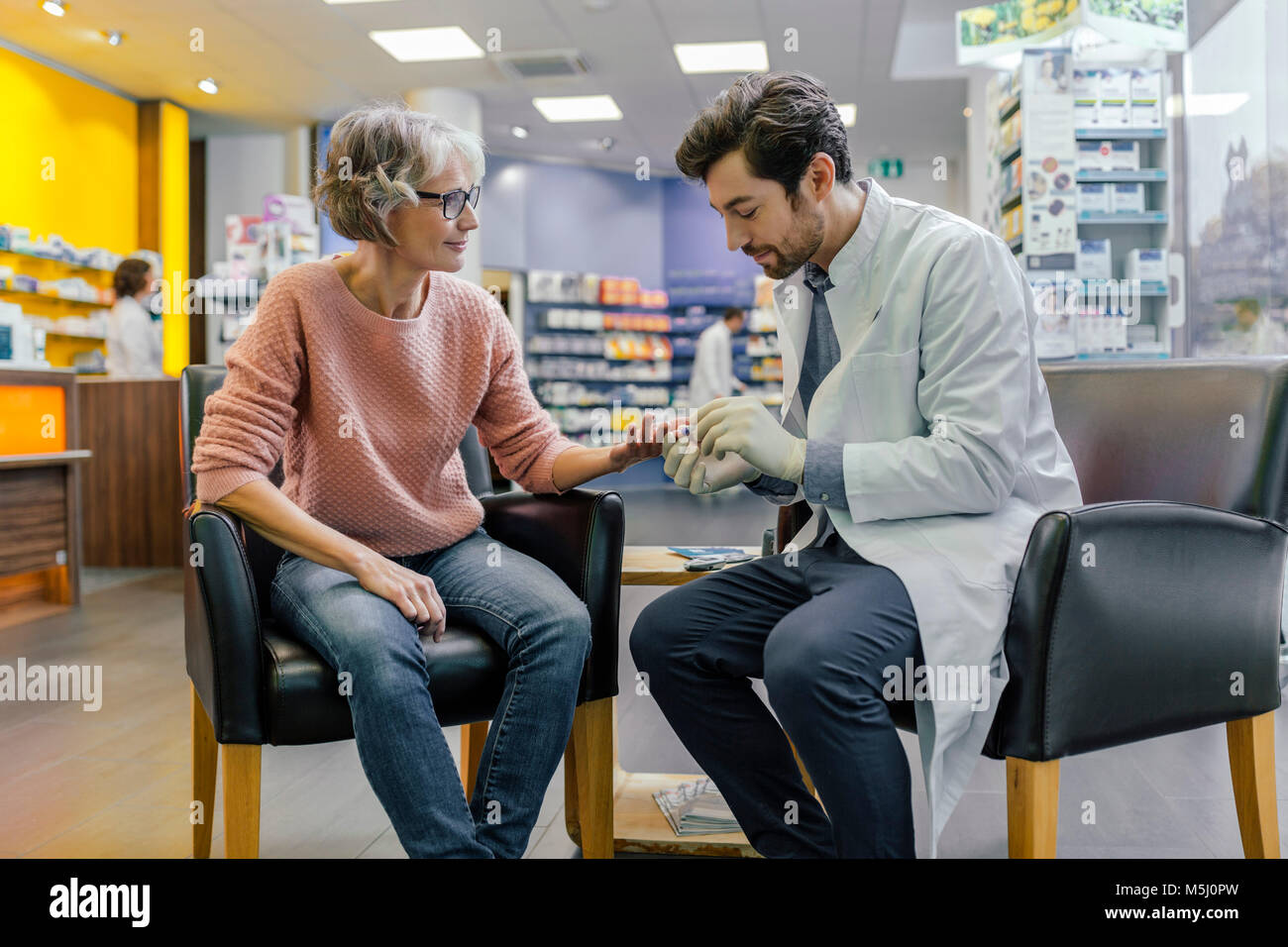 Pharmacist measuring blood sugar of customer in pharmacy Stock Photo