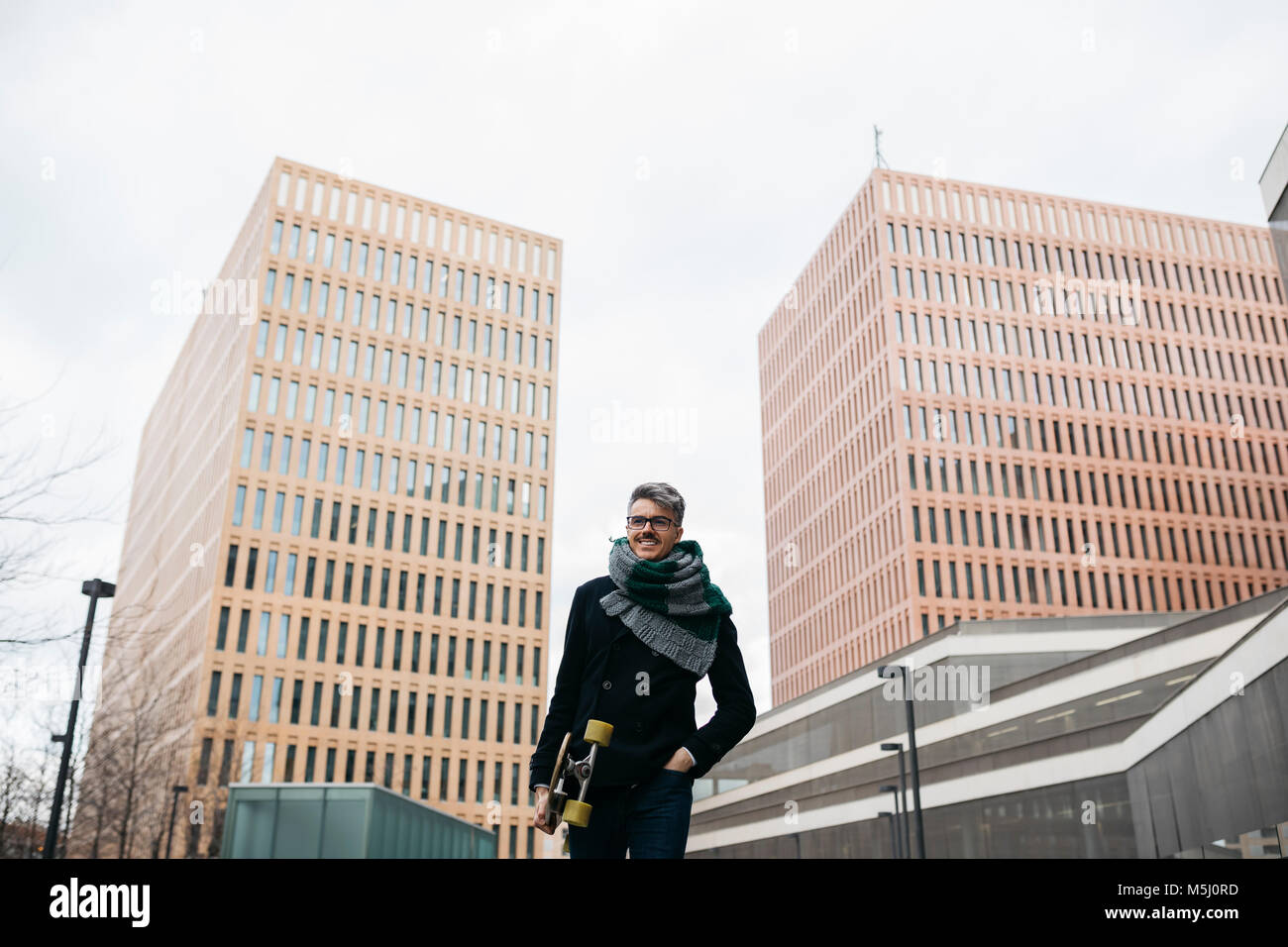 Smiling businessman walking through the city with a longboard - Stock Image